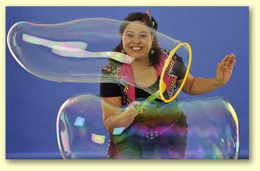 Small photo of Bernadette making large, long bubbles.