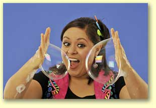 Photograph of Bernadette with a soap bubble on each hand.