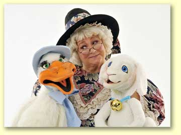 Photo of Mother Goose listening to Goosey (a puppet) with Lamby (a puppet) as well.