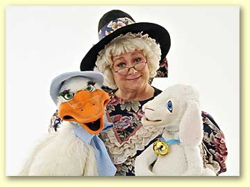 Photo of Mother Goose (played by Margaret Clauder) with Goosey and Lamby perched on her lap.