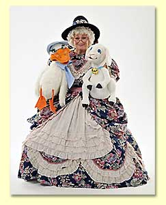 Photograph of Margaret Clauder as Mother Goose, posing with 2 puppets in her lap.